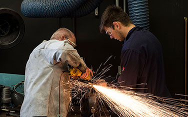 man wearing white overalls using a grinding tool with sparks. Younger male on right in blue overalls watches on