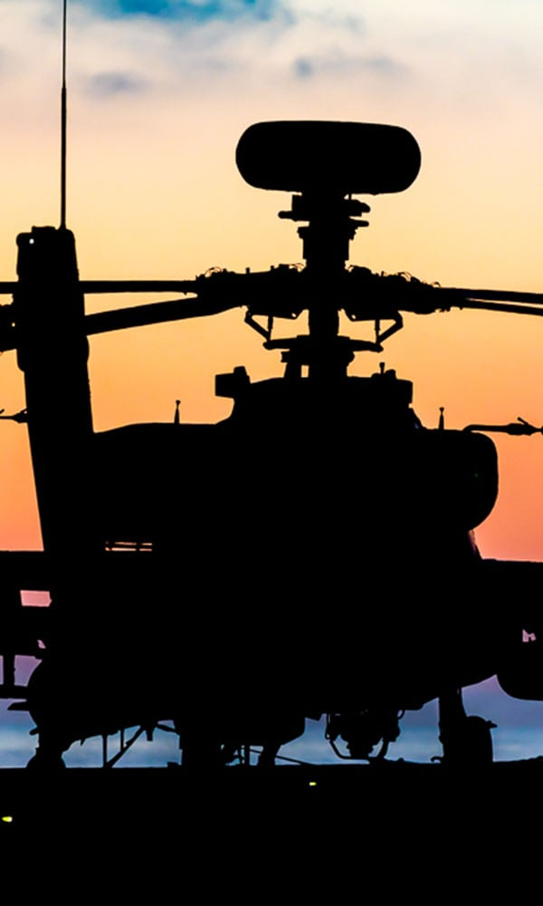 silhouette of apache helicopter at sunset