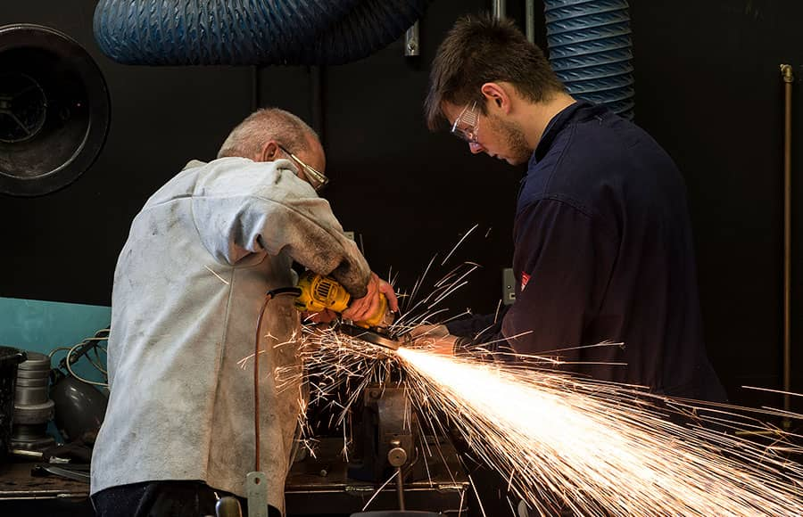 Sparks fly as two men use a metal grinder