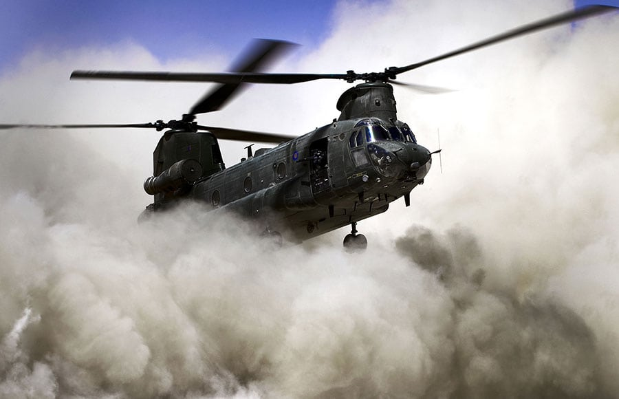 A helicopter lands kicking up a large amount of dust