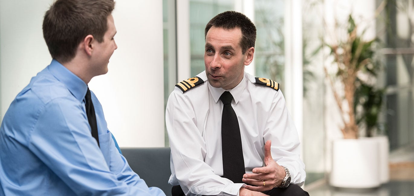 A naval officer interviews a young man in a blue shirt