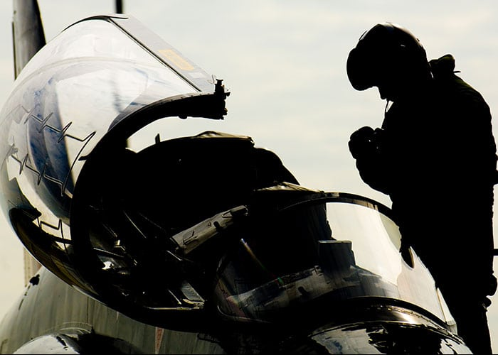 silhouette of pilot getting into cockpit
