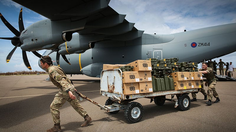 soldier pulls boxes on a truck in front of an a400m aircraft