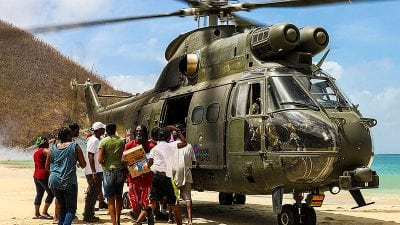 hurricane relief armed forces helicopter distributing aid to locals on a caribbean beach