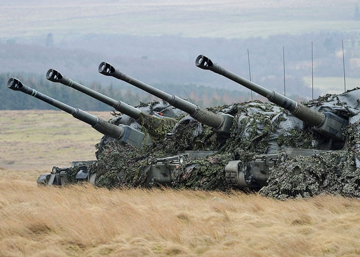 British Army Artillery systems line up in a field.