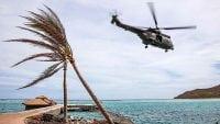 RAF Puma helicopter flies over Caribbean beach after hurricane