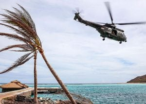 RAF Puma helicopter flies over Caribbean beach after hurricane