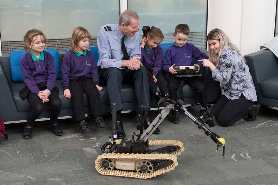 Leaders Award - DE&S's Julian Young sat talking to primary children watching a robot