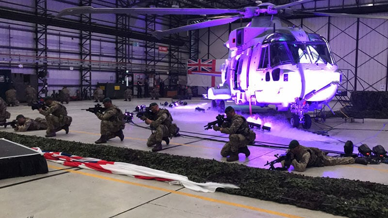 A helicopter lit up by a purple light in a hangar, as soldiers with guns pose in front of it