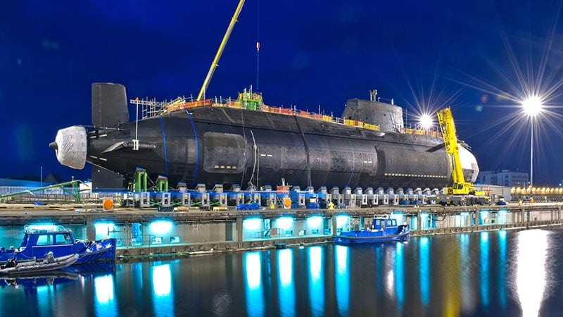 Submarine being lowered into the sea at night