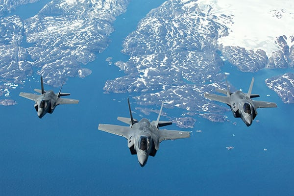 Three fighter jets seen from above flying in formation