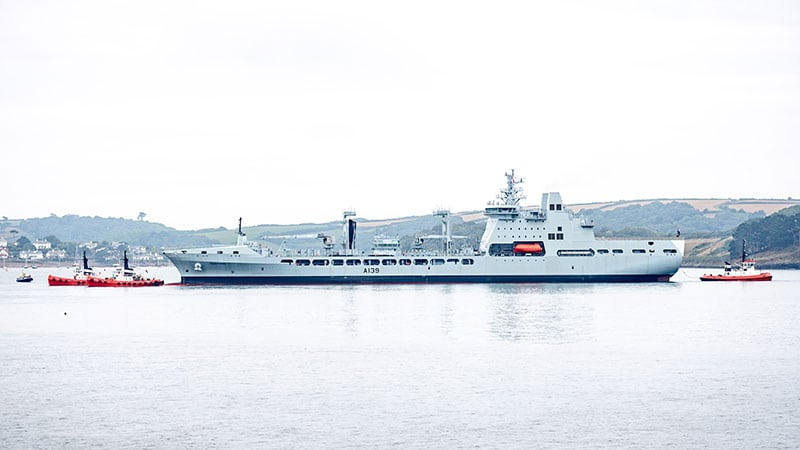 A long grey ship in still harbour waters