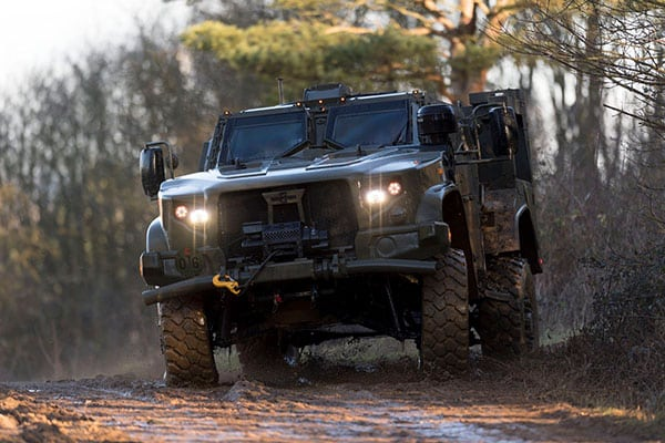 A military jeep bouncing over mud