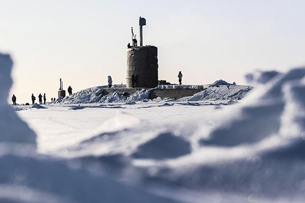 A black submarine breaks through the ice