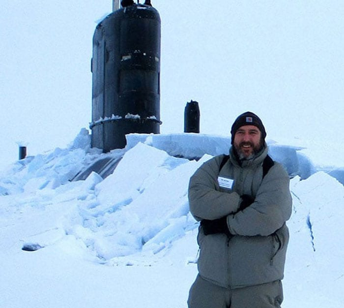 Man stood infant of a submarine in the artic competing in ICEX