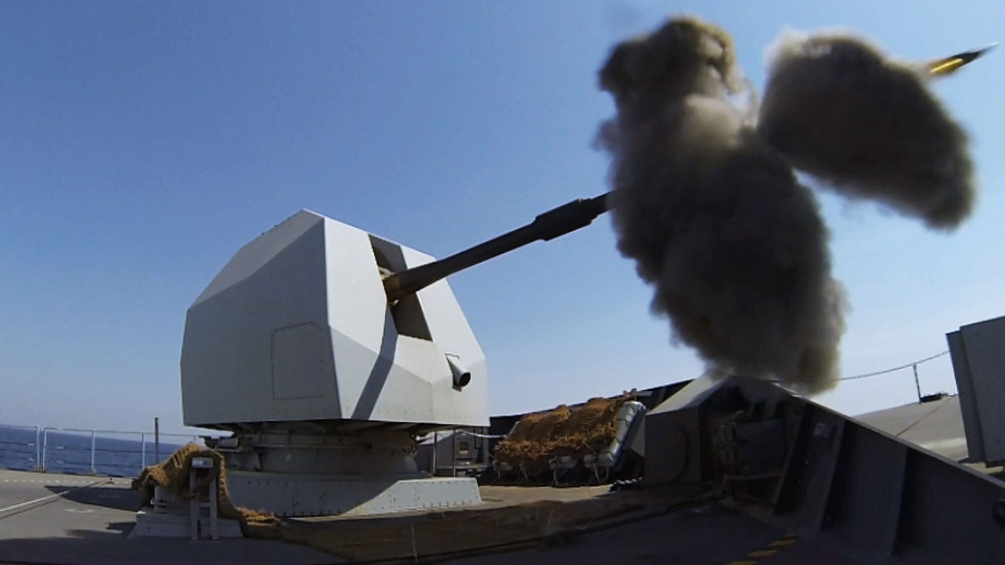 "Mark 8 naval gun firing a 4.5"" shell out to sea from Royal Navy ship"