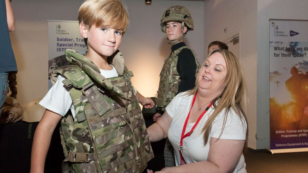 Child tries on army body armour