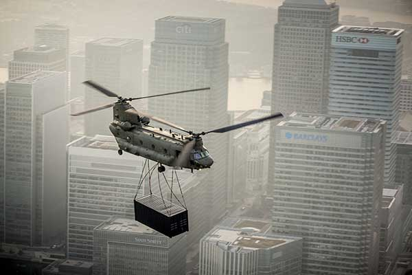A military twin rotor helicopter flying with cargo against a backdrop of skyscrapers in London