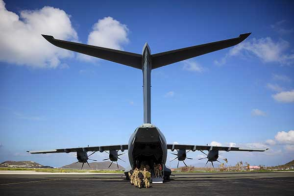 Soldiers enter the back of a military aircraft