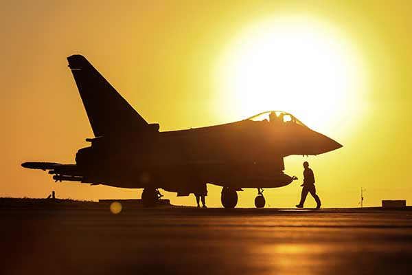A fighter jet silhouetted against the sun