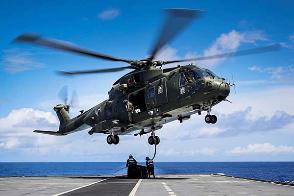 A military helicopter hovers above a flight deck