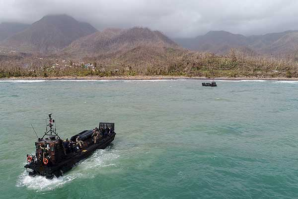 A small military boat approaches a tropical island