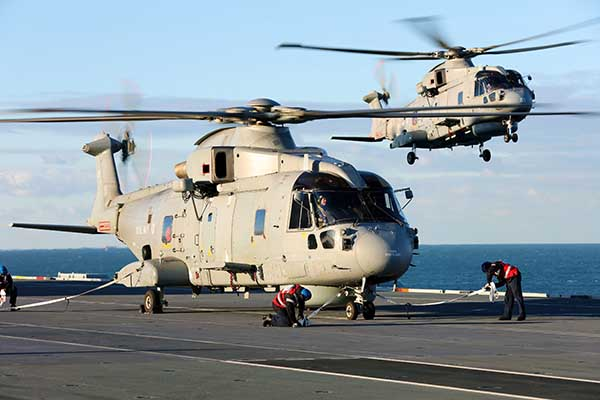 A helicopter sits on a flight deck as another one hovers next to it.