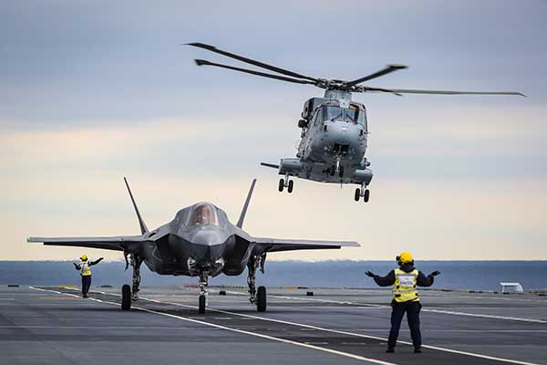 A military jet sits on a flight deck as a helicopter takes off behind it.