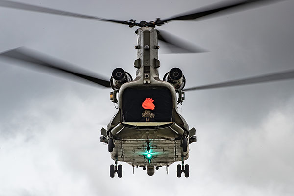 A twin rotor helicopter flying against a grey sky, with its rear door open and a solider visible inside