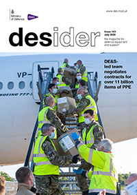 The front cover of July's Desider magazine showing a number of people in high-visibility jackets carrying boxes and walking up a large set of stairs leading to an airplane