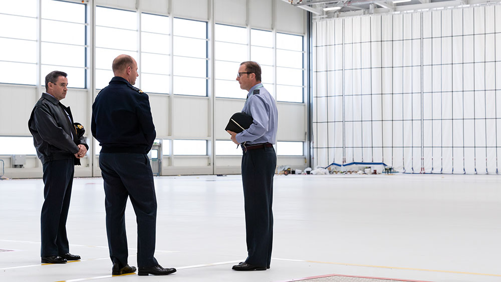 A large white hangar space with three men standing in the foreground