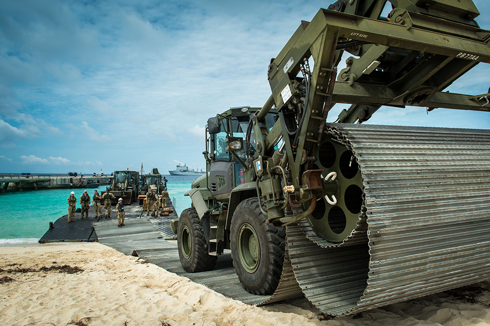 A bulldozer laying a temporary road on a tropical beach, having arrived on the sand via landing craft