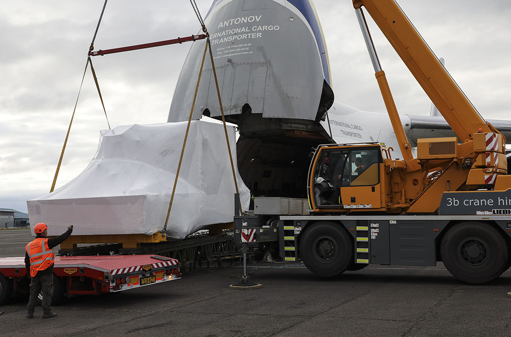 The nose of the world's largest aircraft is open with a large flight simulator wrapped in plastic on a cargo pallet emerges
