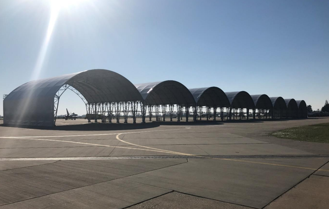 A line of empty hangars stand in the sunshine on an airfield