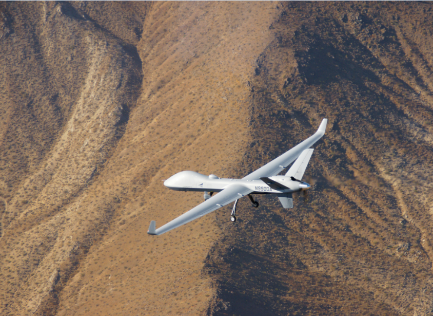 White unmanned aircraft flying over plain brown desert mountains