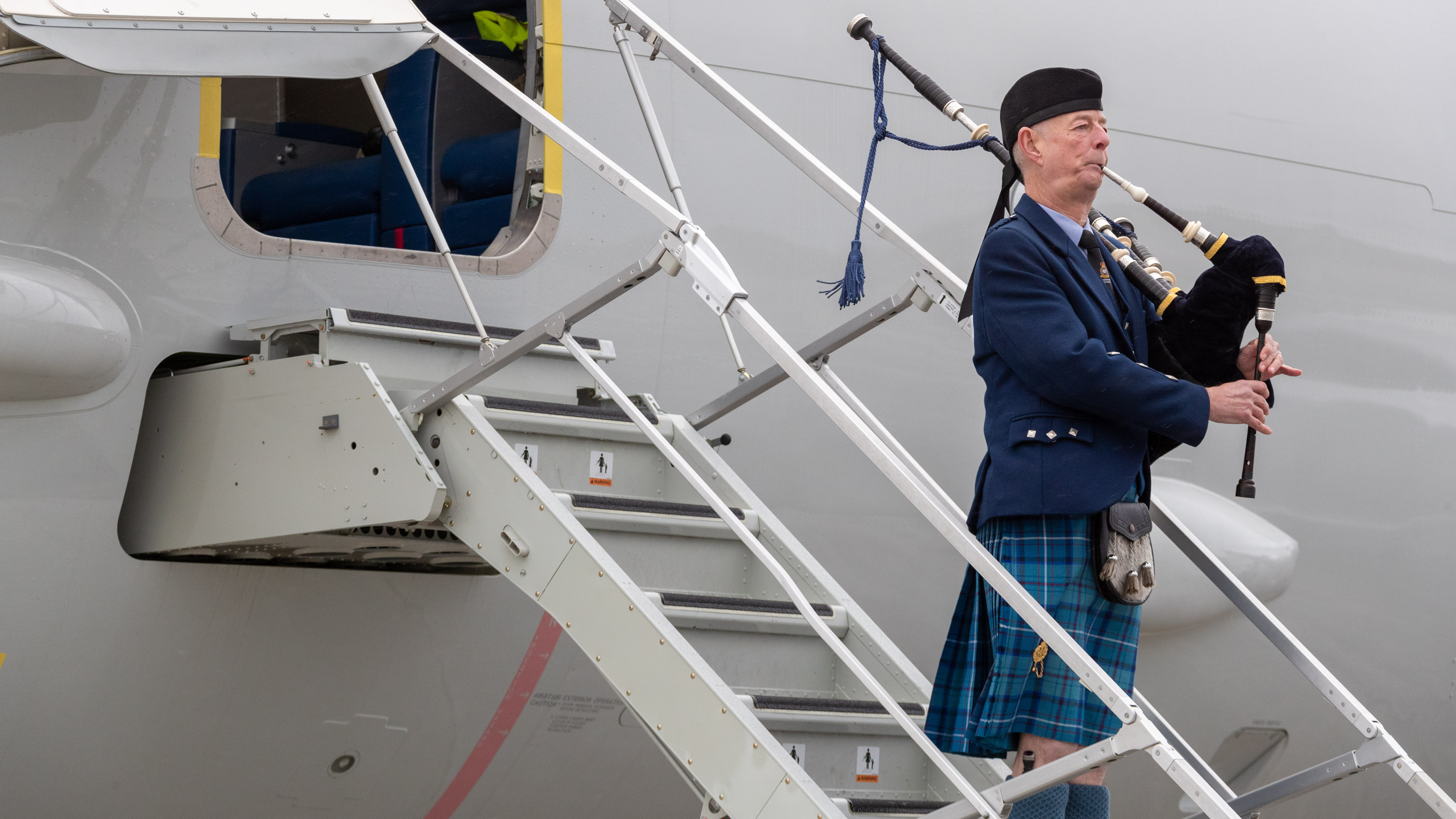 A bagpiper plays after ZP802, the City of Elgin, touches down at RAF Lossiemouth for the first time